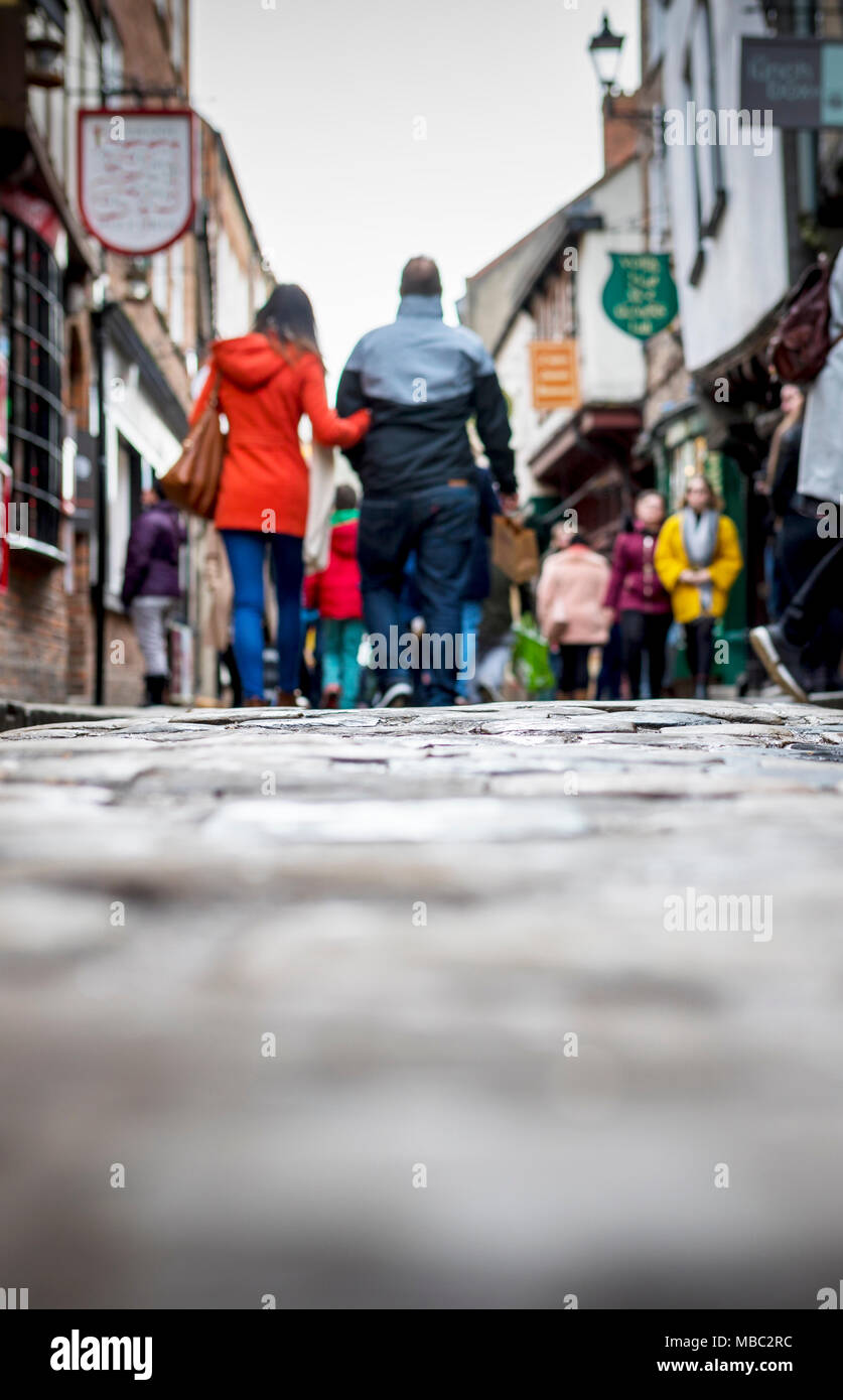 Low down shot of people and couple walking holding hands down a old traditional cobbled English street whilst browsing in shops on retail therapy day  - Stock Image