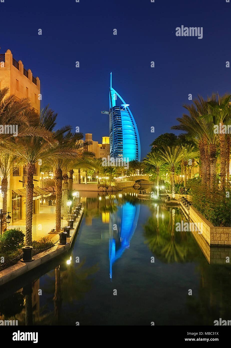 DUBAI, UAE - APR 8, 2013: Famous reflection view with 7 star hotel Burj Al Arab. Night scene with palms. Colorful canal resort. Dubai, United Arab Emi - Stock Image
