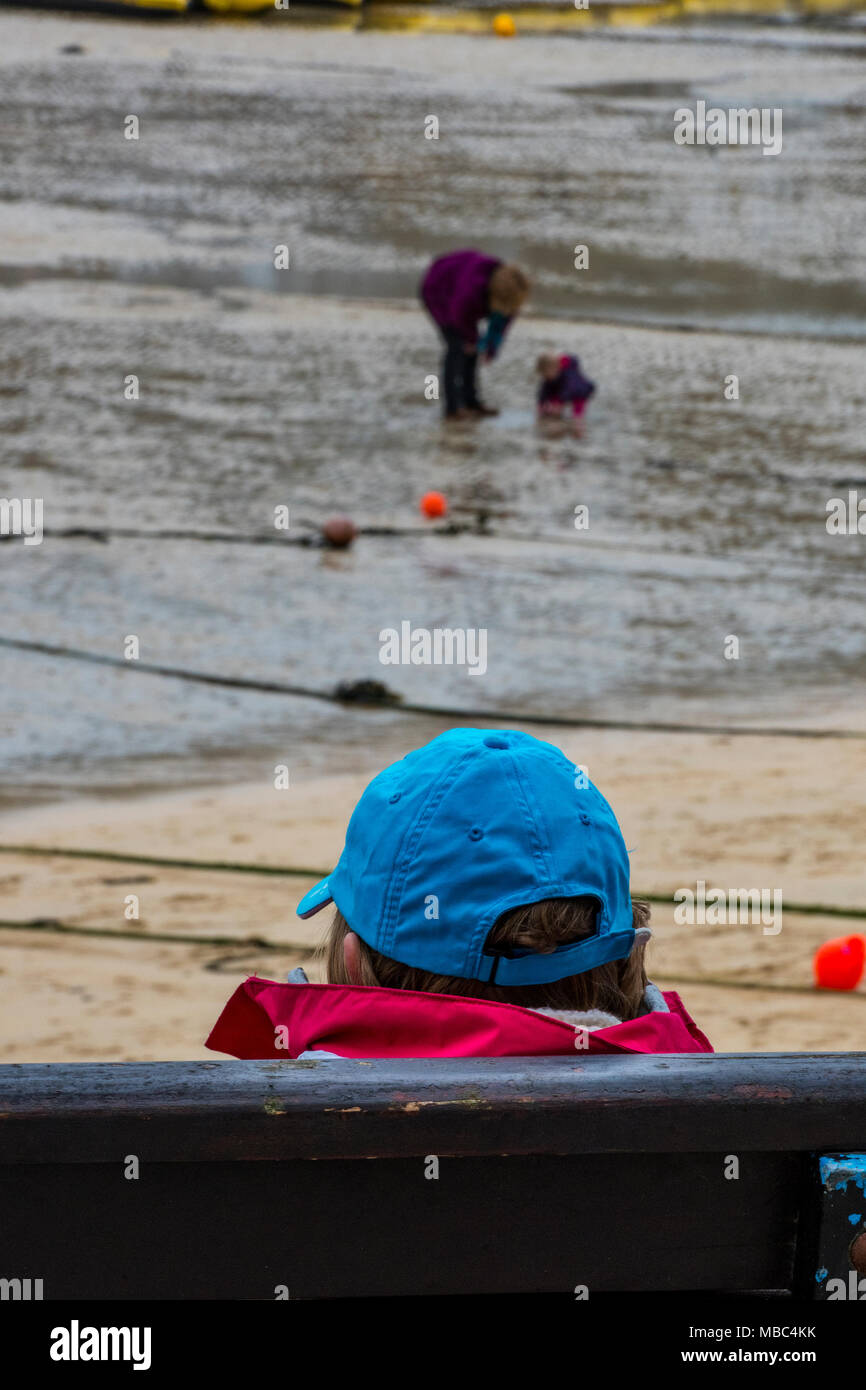 An older or elderly man sitting at the seaside on a bench looking out over the harbour at people playing on the beach. Wearing a blue baseball cap. - Stock Image