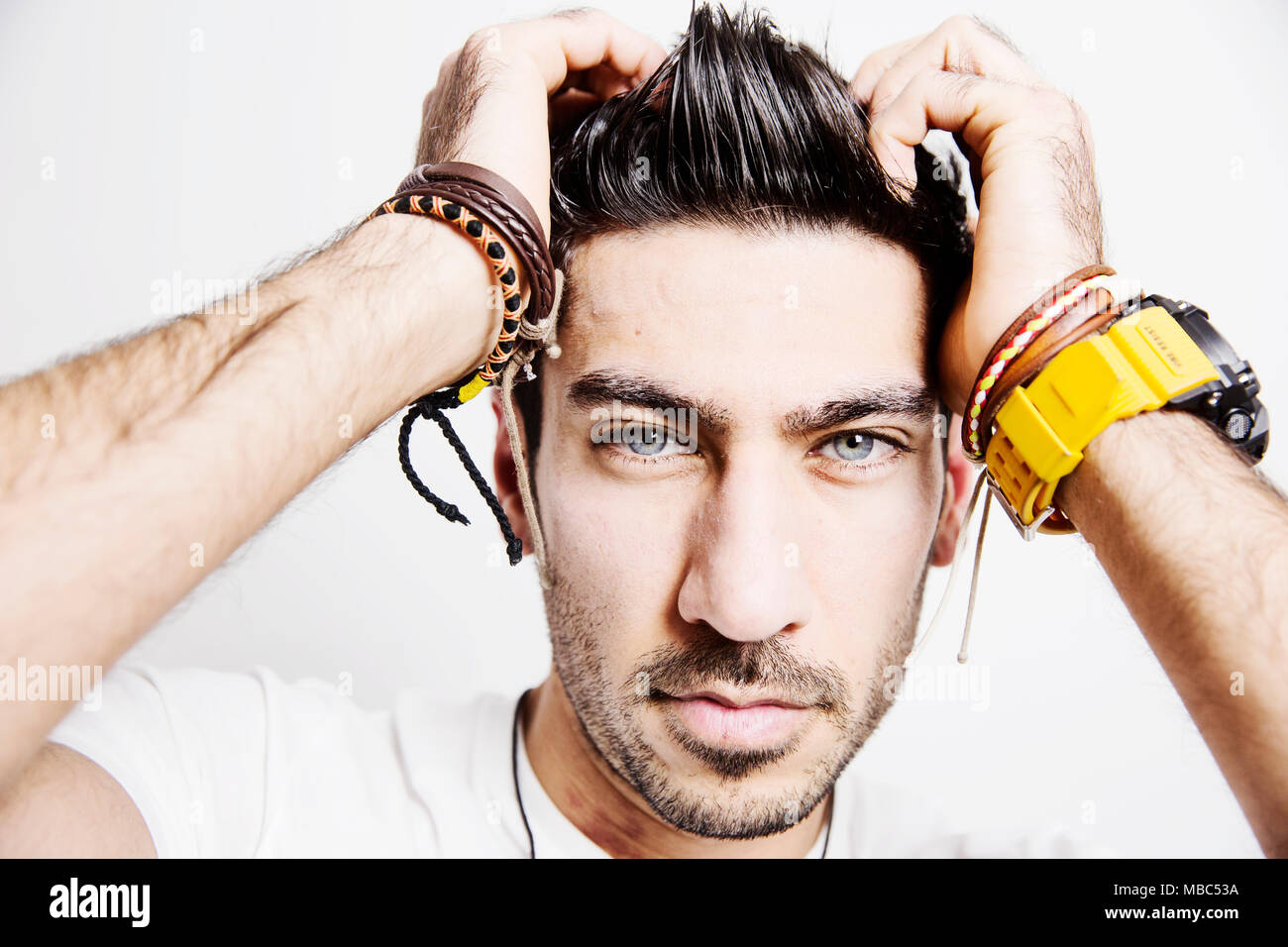Young man, sporty watch and friendship straps, grabs his hair, portrait, studio shot - Stock Image