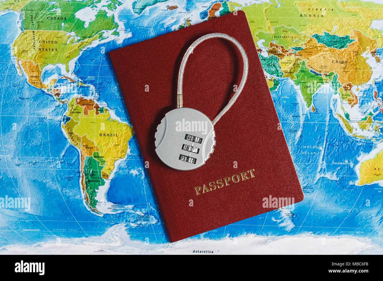 Code Lock on Red Passport on World Map Background. Concept-Ban on Travel, Lack of Visa. - Stock Image