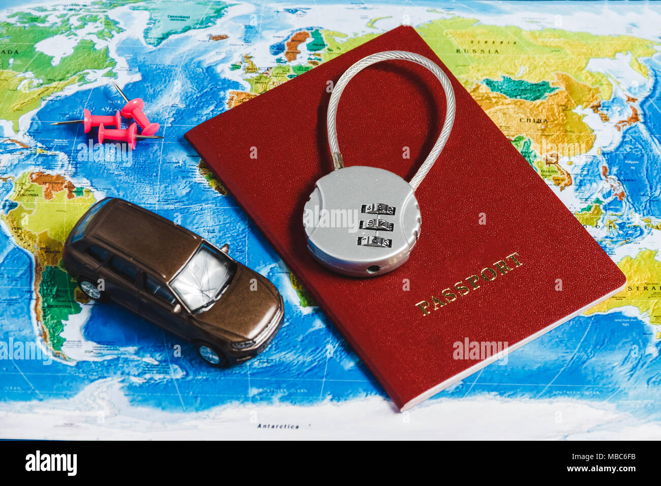 Code Lock on Red Passport, Toy Car, Pushpins on World Map Background. Concept-Ban on Travel, Lack of Visa. - Stock Image