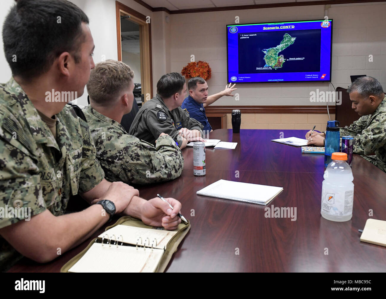 U.S. Coast Guard Lt. Cliff Graham, assigned to USCG, Sector Guam, explains the drift-current complications in a search area off the eastern coast of Guam during a table-top exercise designed to demonstrate interoperability for a joint search and rescue operation, Feb. 16, 2018. CTF 75 is the primary expeditionary task force responsible for the planning and execution of coastal riverine operations, explosive ordnance disposal, diving engineering and construction and underwater construction in the U.S. 7th Fleet area of operations. (U.S. Navy Combat Camera Stock Photo