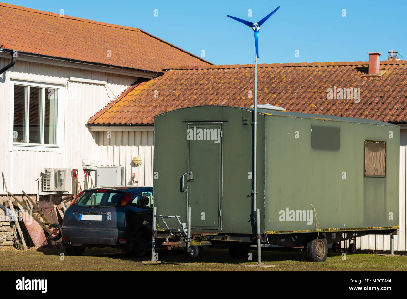 Repurposed military trailer outside a house. Small wind power ...