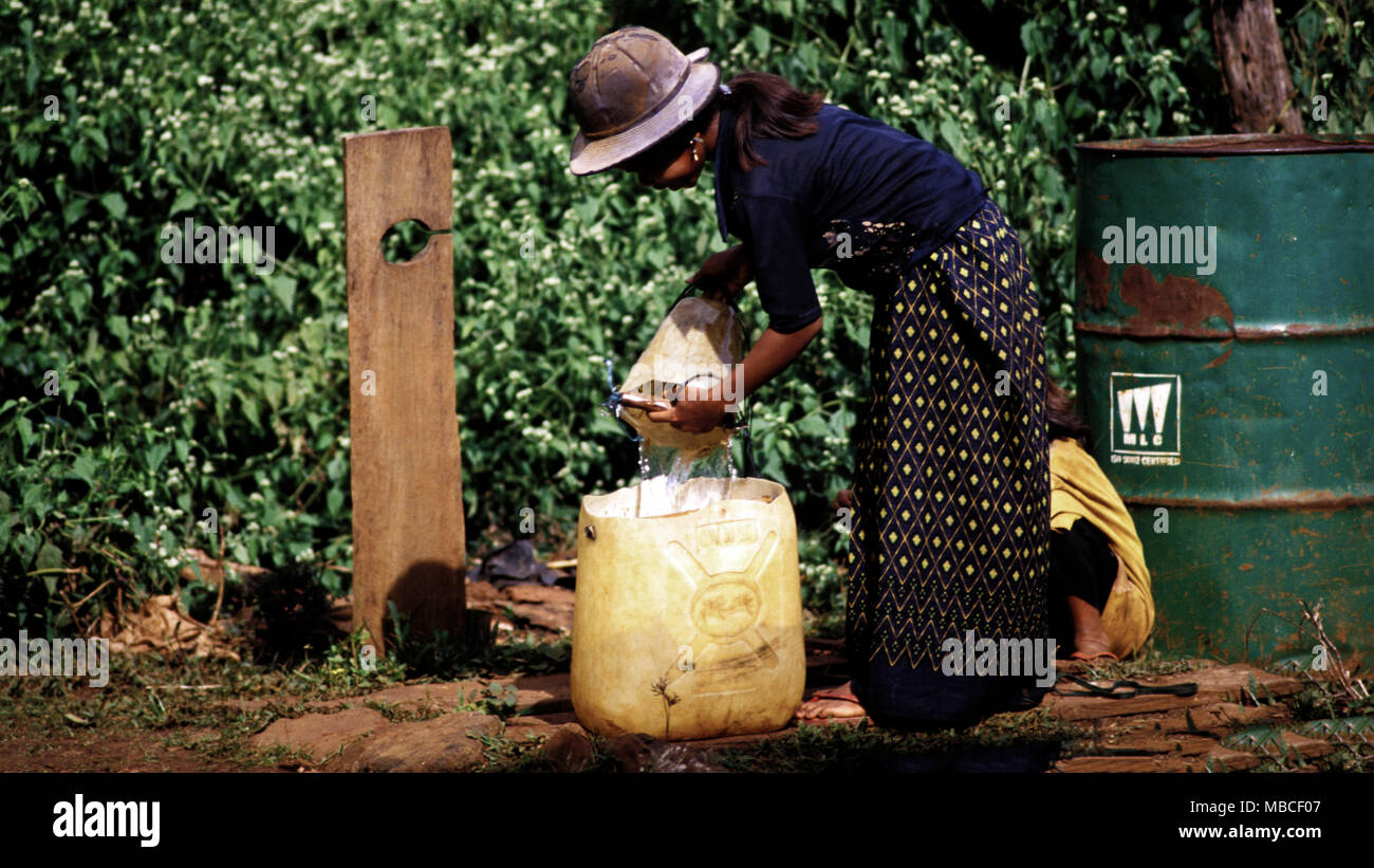 A young, indigenous Mnong (Pnong) girl fetches water from her village well as part of her daily routine. Mondolkiri Province, Cambodia. - Stock Image