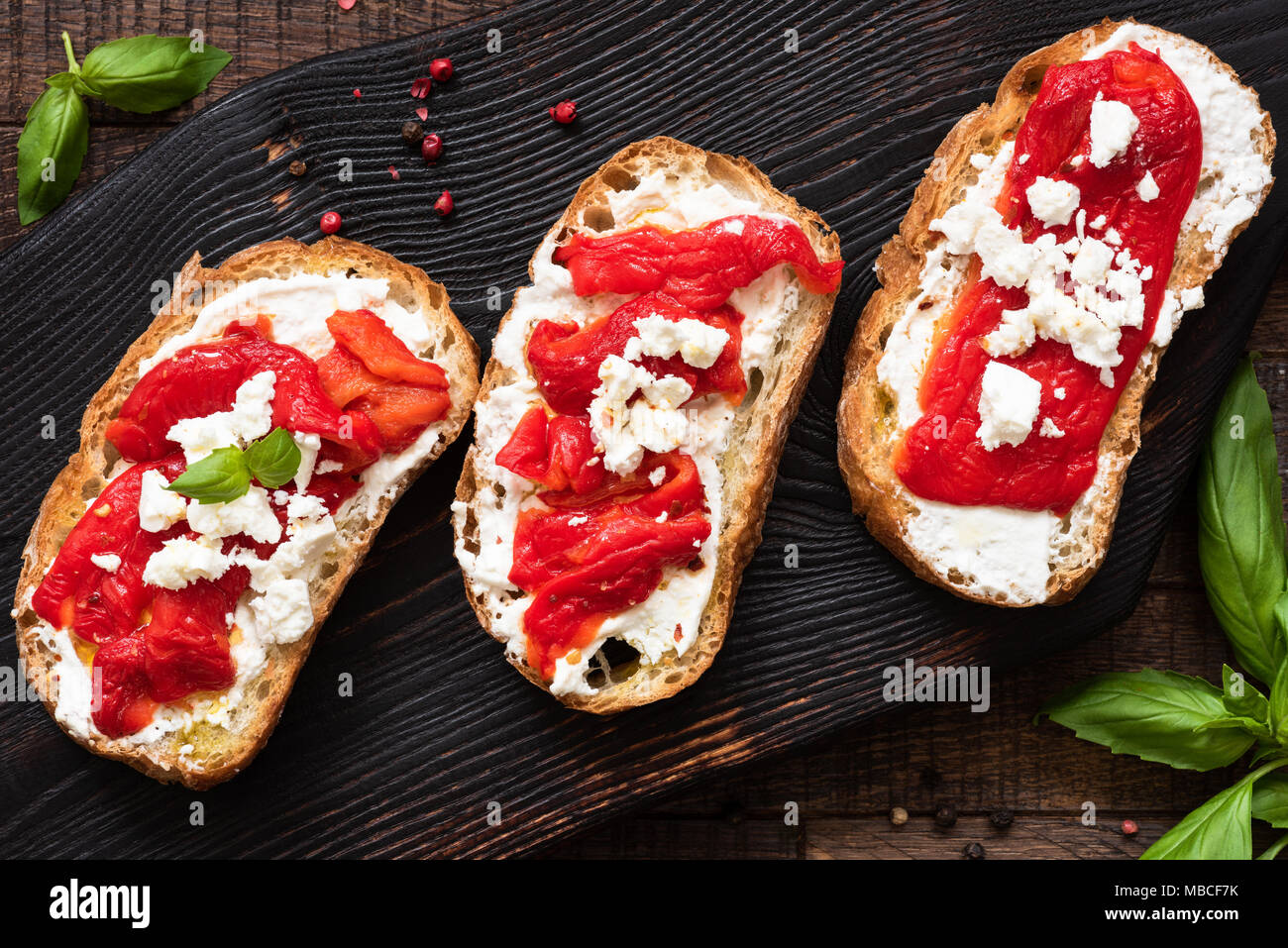 Bruschetta with roasted pepper, feta cheese and olive oil on old wooden cutting board, top view. Italian cuisine appetizer, starter or antipasti - Stock Image