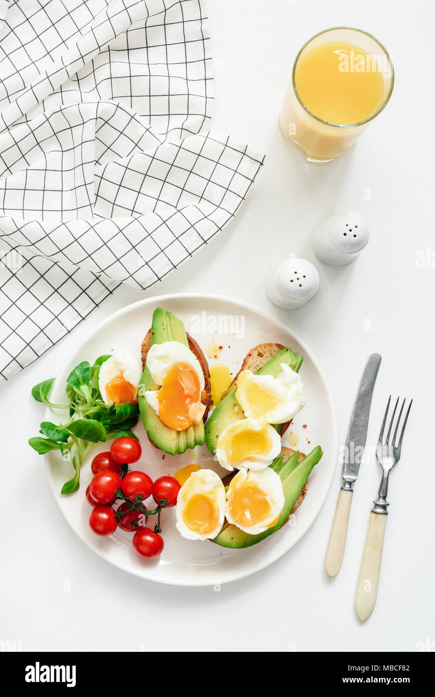 Healthy avocado and egg toasts and orange juice for breakfast on white background. Top view, flat lay, modern healthy lifestyle - Stock Image