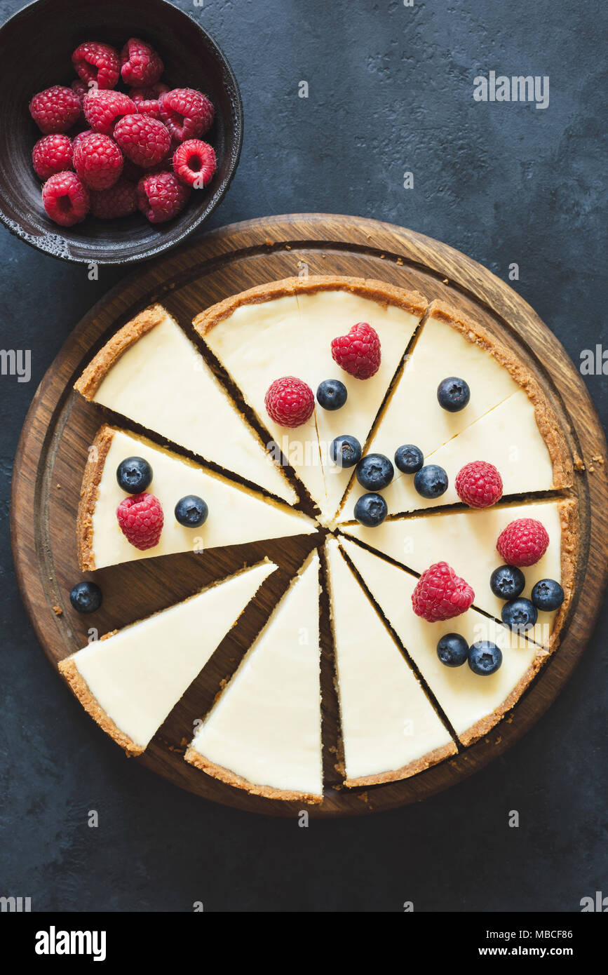 Classical cheesecake with fresh berries on wooden board cut into slices. Top view with copy space for text. Toned image - Stock Image
