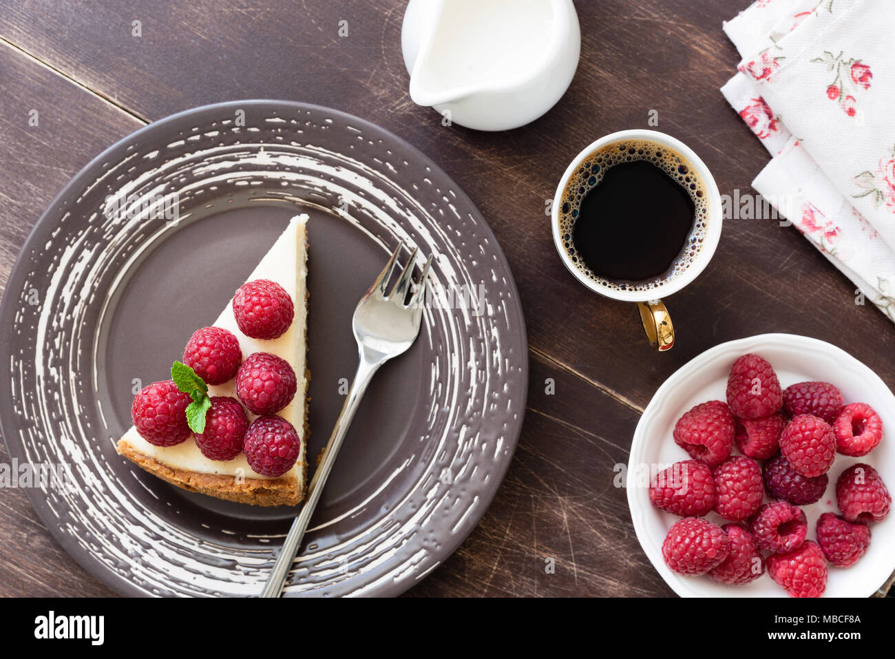 Slice of cheesecake with raspberries and cup of coffee on wood table. Top view - Stock Image