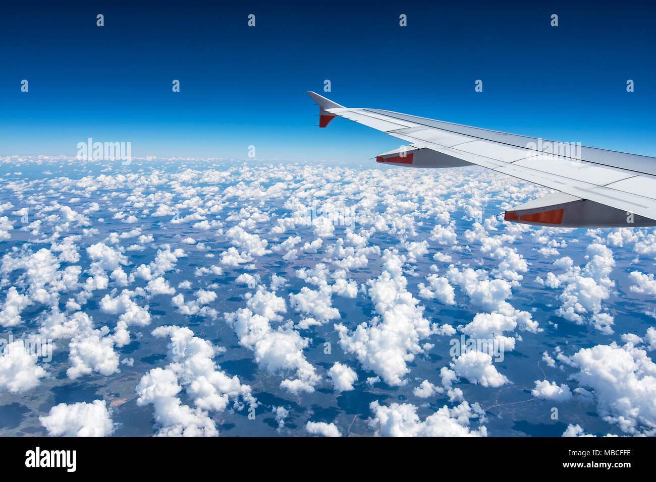 Wing of a commercial airliner flying over fluffy white cumulus clouds, Australia Stock Photo