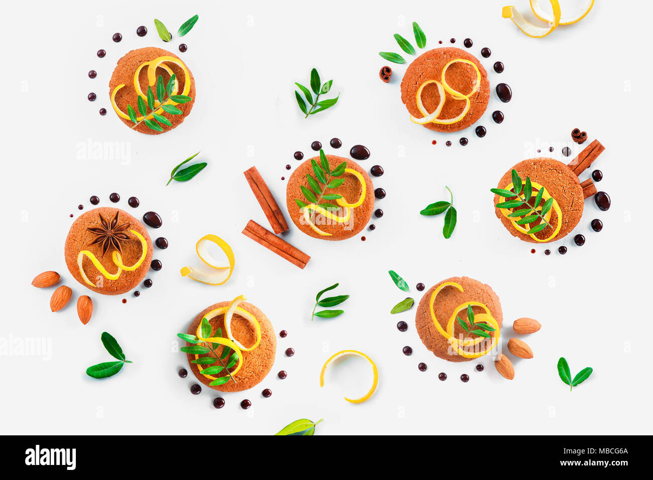 Food styling tips pattern made of cookies, chocolate swooshes and rings, cinnamon, lemon zest and green leaves. Cookie decoration concept - Stock Image