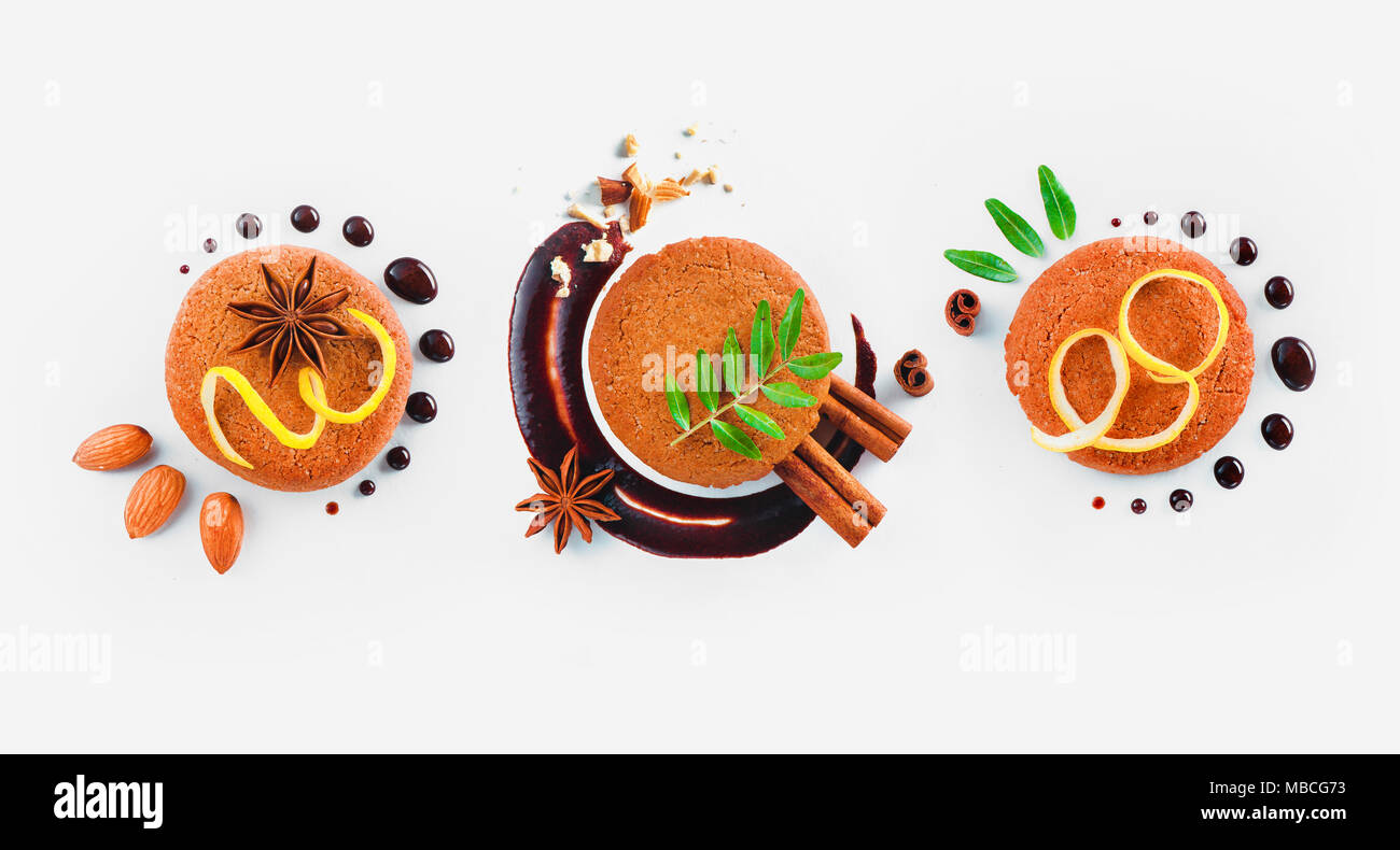 Cookie decoration flat lay. Food styling tips pattern made of cookies, chocolate swooshes and rings, cinnamon, lemon zest and green leaves. - Stock Image