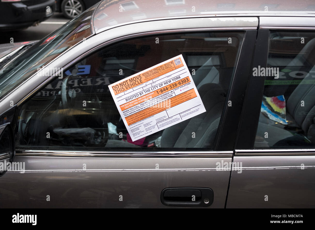 A notice on a parked car in Cobble Hill, Brooklyn that has been booted by the City for parking violation or violations. - Stock Image