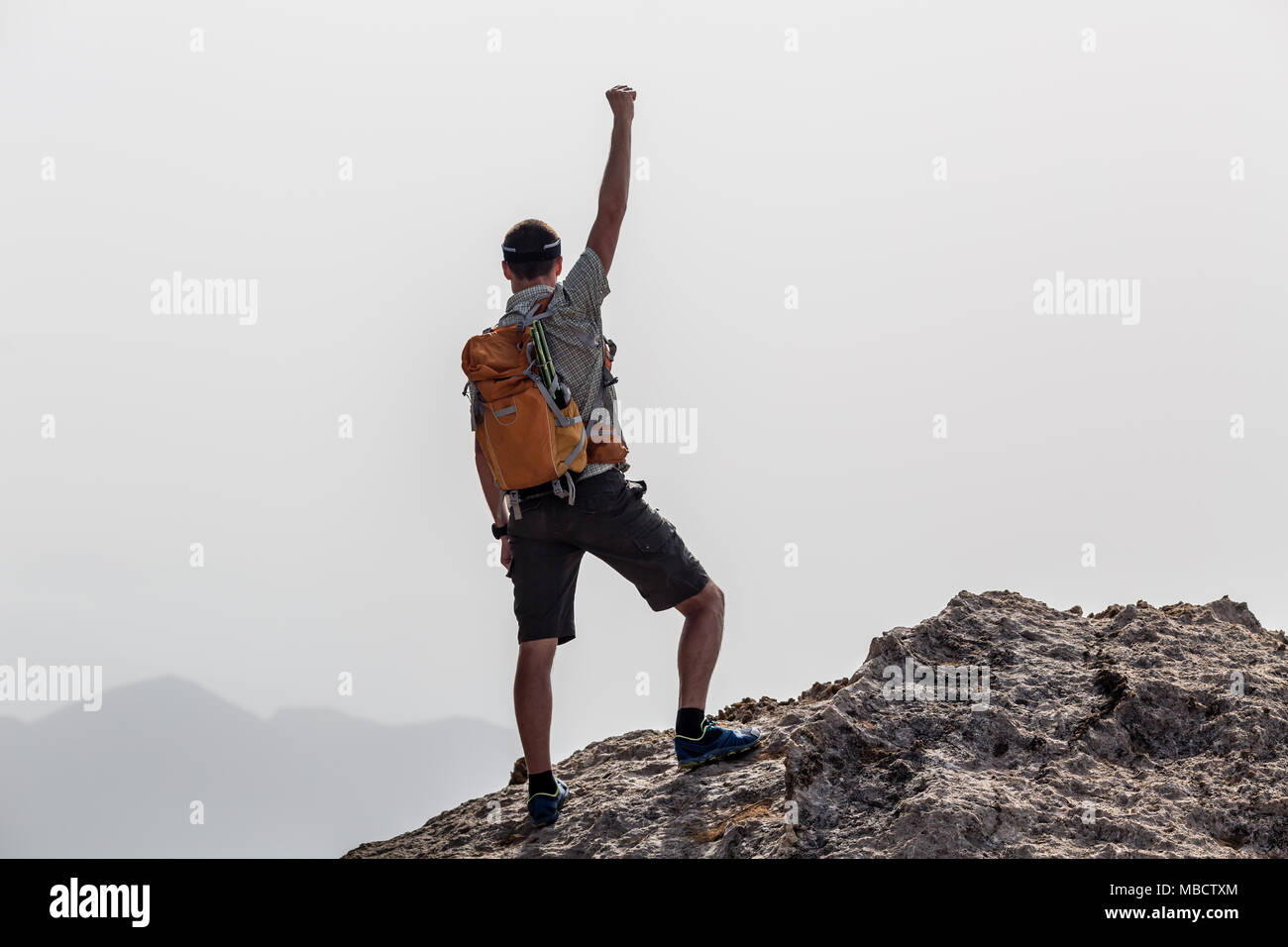 Success and achievement business concept with man celebrating with hand up, arm raised outstretched looking at inspirational landscape view, Greece. - Stock Image