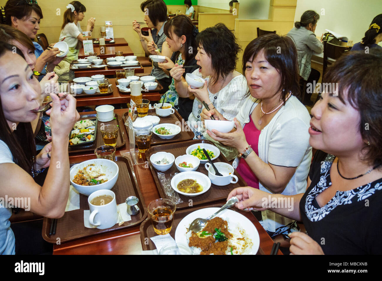 Tokyo Japan Shinjuku Shinjuku NS Building restaurant office workers Asian woman women co-workers eating dining - Stock Image