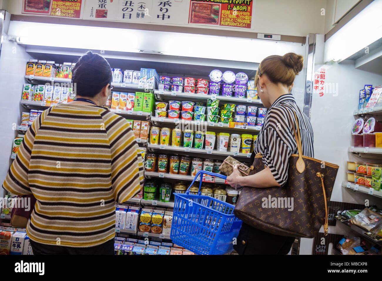Tokyo Japan Shinjuku Lawson Convenience Store shopping shoppers kanji hiragana katakana characters symbols Japanese English reta - Stock Image