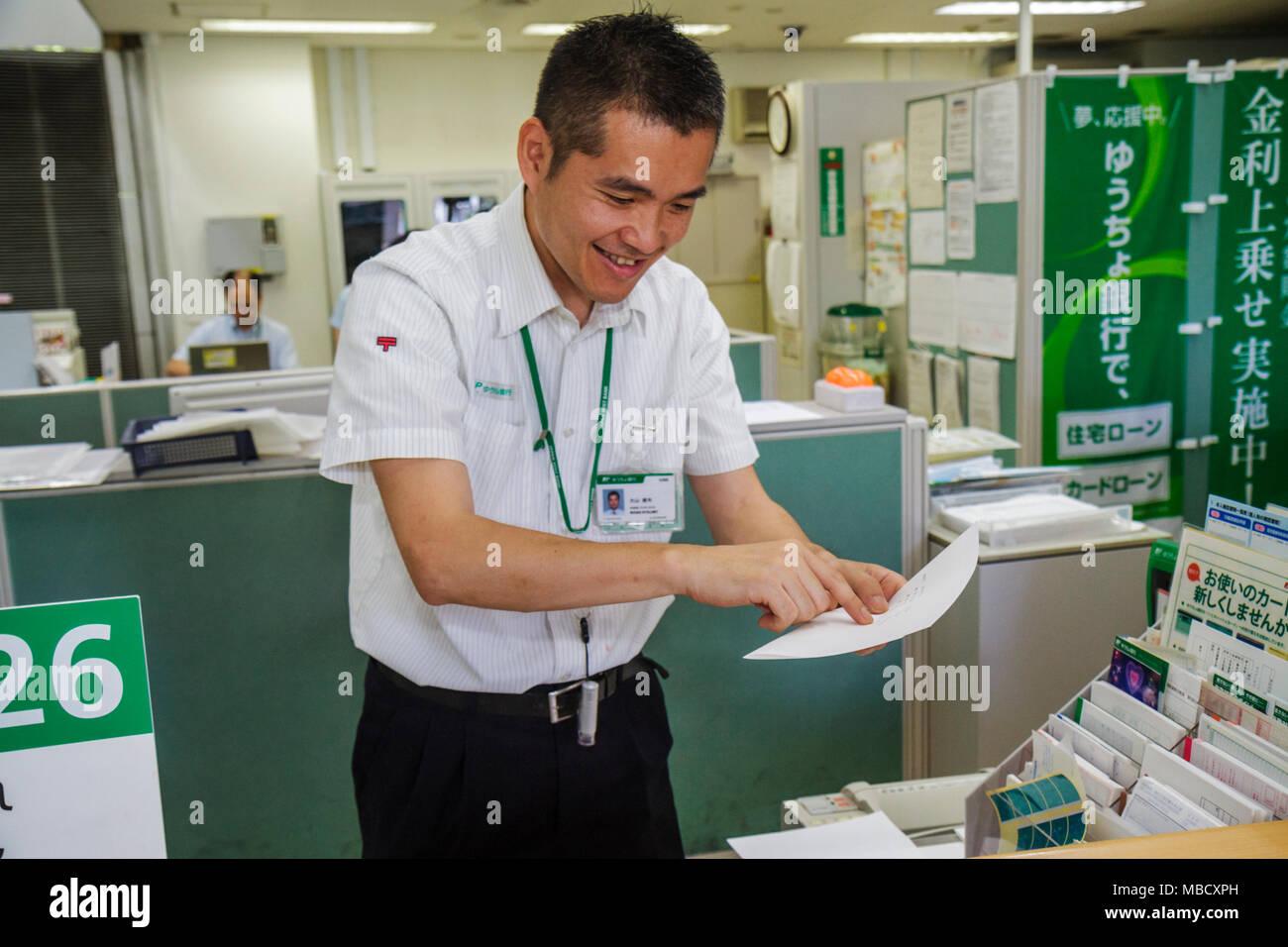 Tokyo Japan Shinjuku Post Office JP Bank kanji hiragana katakana characters symbols Japanese English Asian man postal worker cou - Stock Image