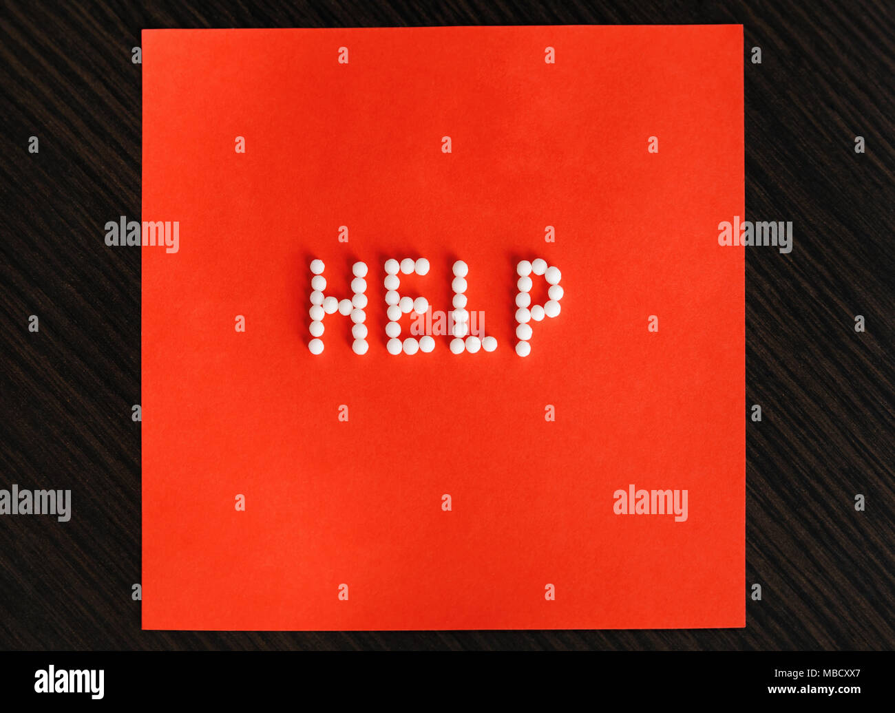 Help Homeopathy. The word 'help' set out with homeopathic balls on a red background. - Stock Image