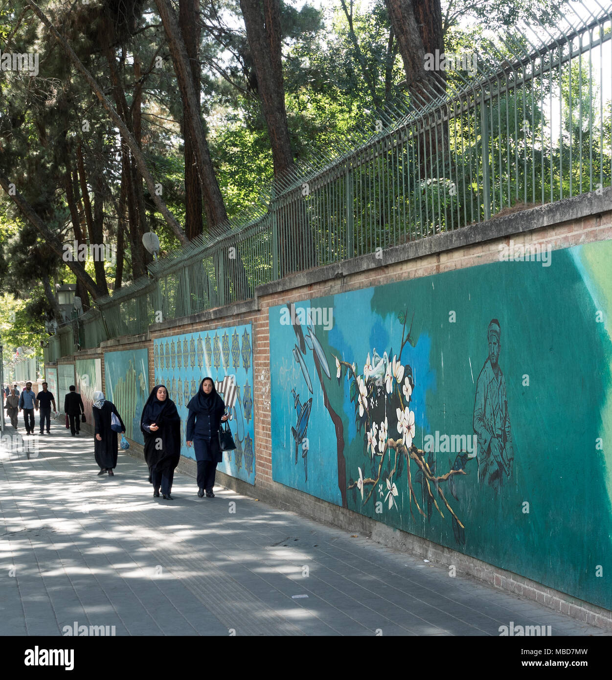 Tehran, Iran - July 16, 2016 : Sidewalk next to abandoned US embassy with propaganda murals - Stock Image