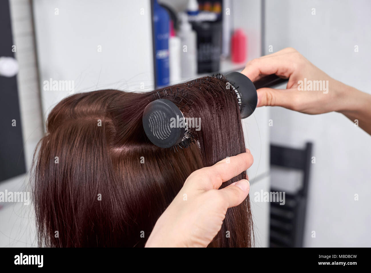 Closeup of hair dresser combing client's hair in salon - Stock Image
