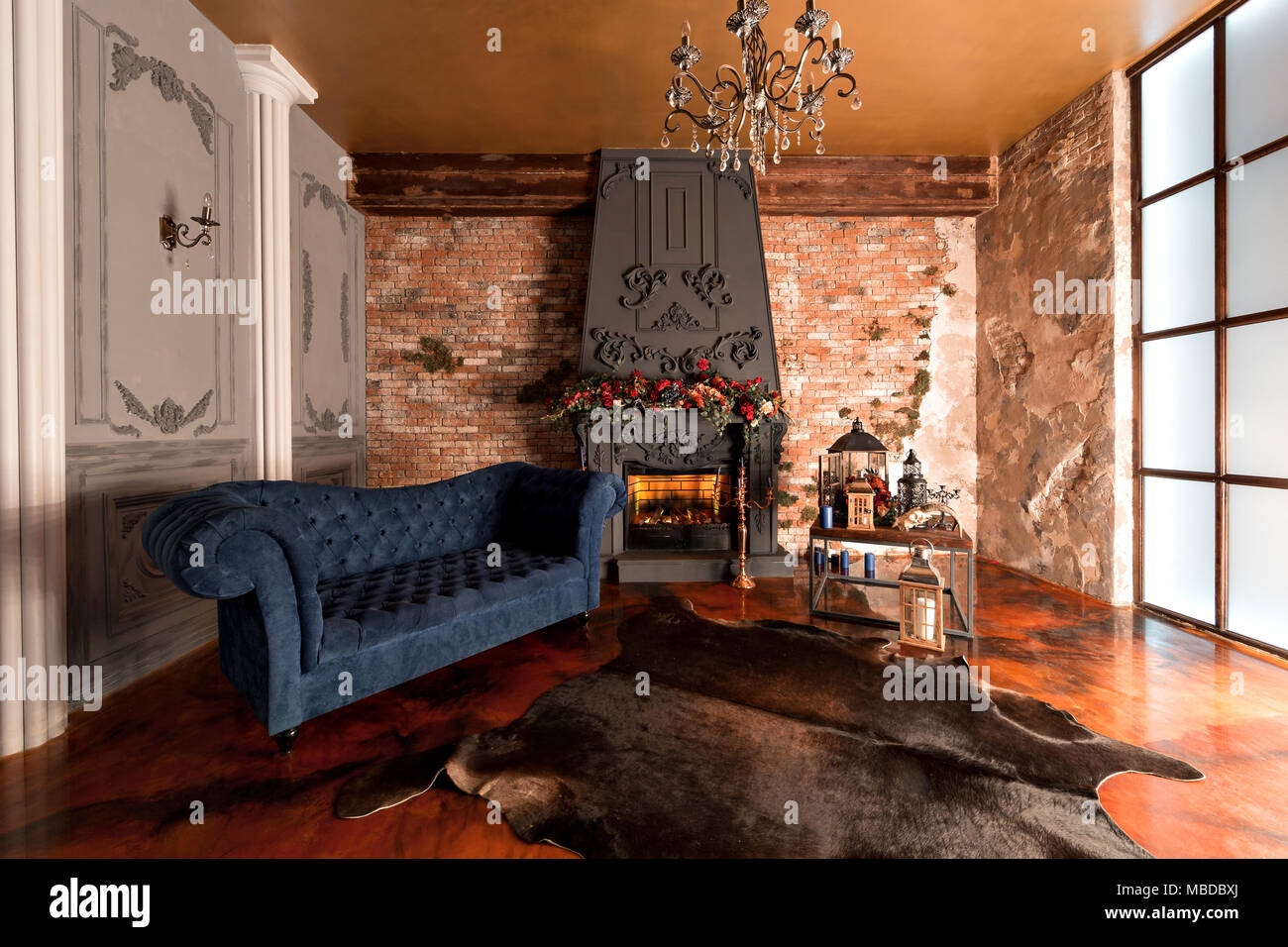 Good Interior With Fireplace, Candles, Skin Of Cows, Brick Wall, Large Window  And A Living Room, Coffee Table And Dark Blue Sofa In Modern Design.