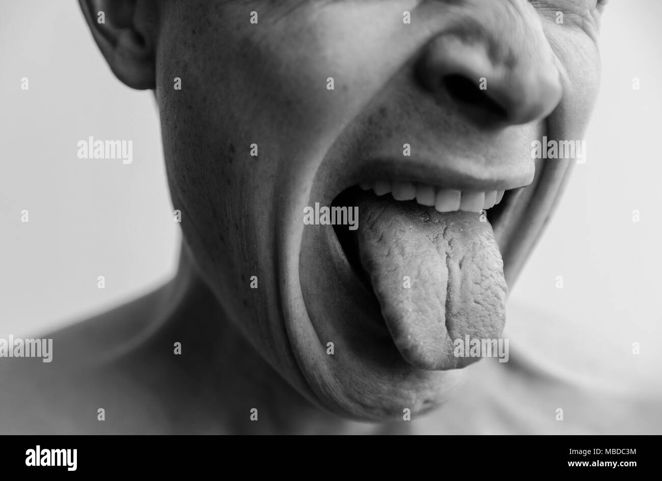 Mimicry, showing disgust . The lower part of the face of a man closeup. Black and white images - Stock Image