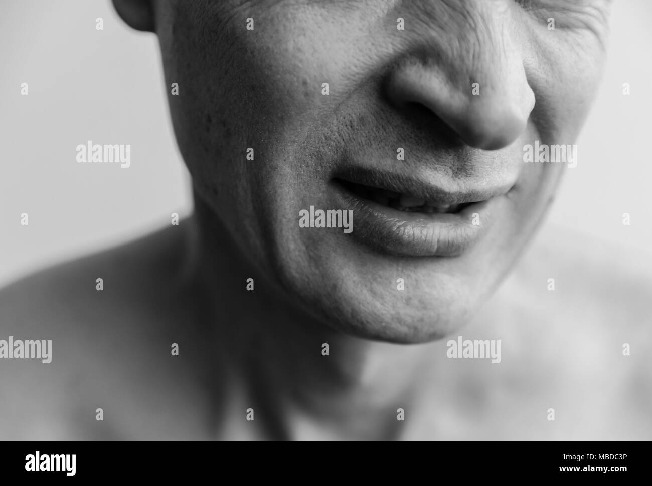 Mimicry showing  not like. The lower part of the face of a man closeup. Black and white images - Stock Image