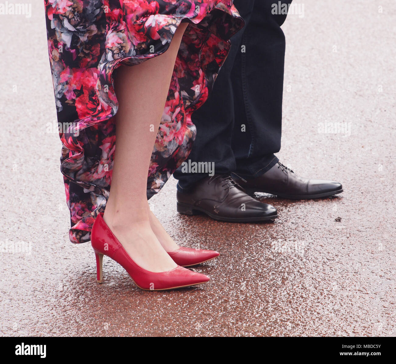 A woman's lower legs, flowery dress and red stiletto heels standing next to a man's legs in trousers and dress shoes on wet  paving - Stock Image