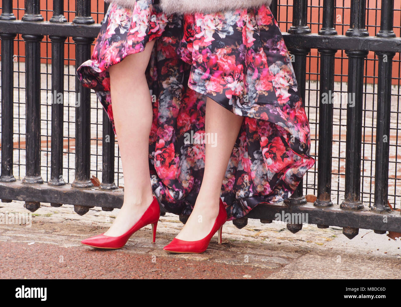 A young woman's legs and ankles wearing red stiletto heels and a flowery dress in front of heavy metal railings at Buckingham Palace, London - Stock Image