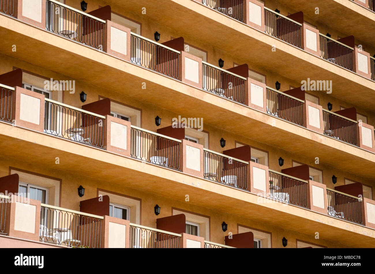 A close up view of balconies belonging to a hotel in Santa Susanna, Spain uniformly laid out with picnic tables and chairs. - Stock Image