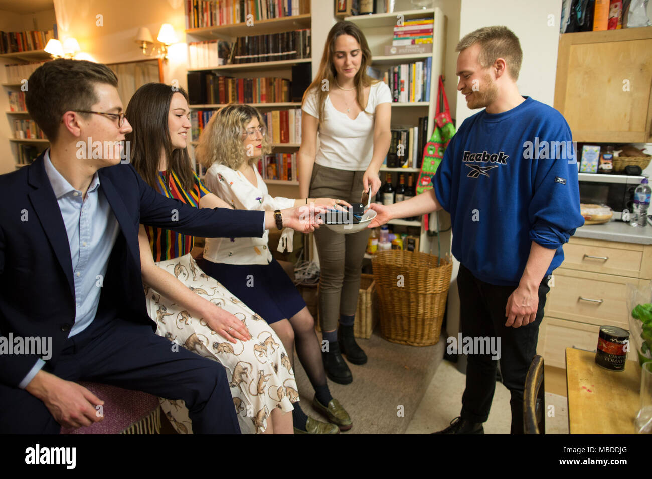 Young group of people attending a dinner party hand their smartphones into the host for a 'smartphone free' evening, London, UK - Stock Image