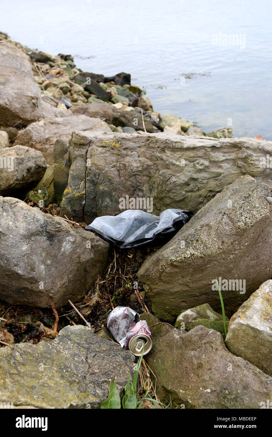 Empty can and plastic on rocks by the coast. - Stock Image
