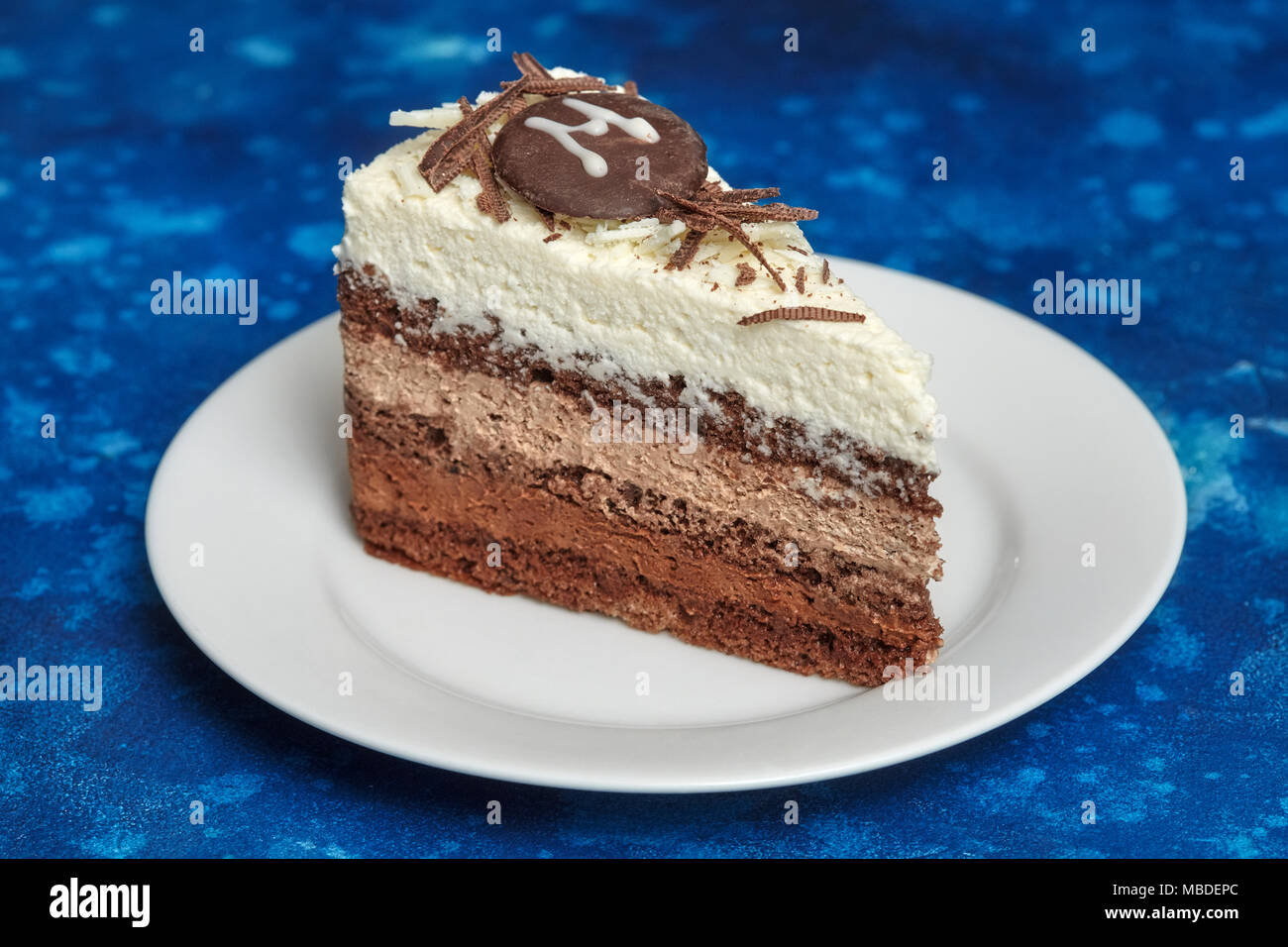 Piece of delicious mousse cake with three different kind of chocolate on white plate. Blue background Stock Photo