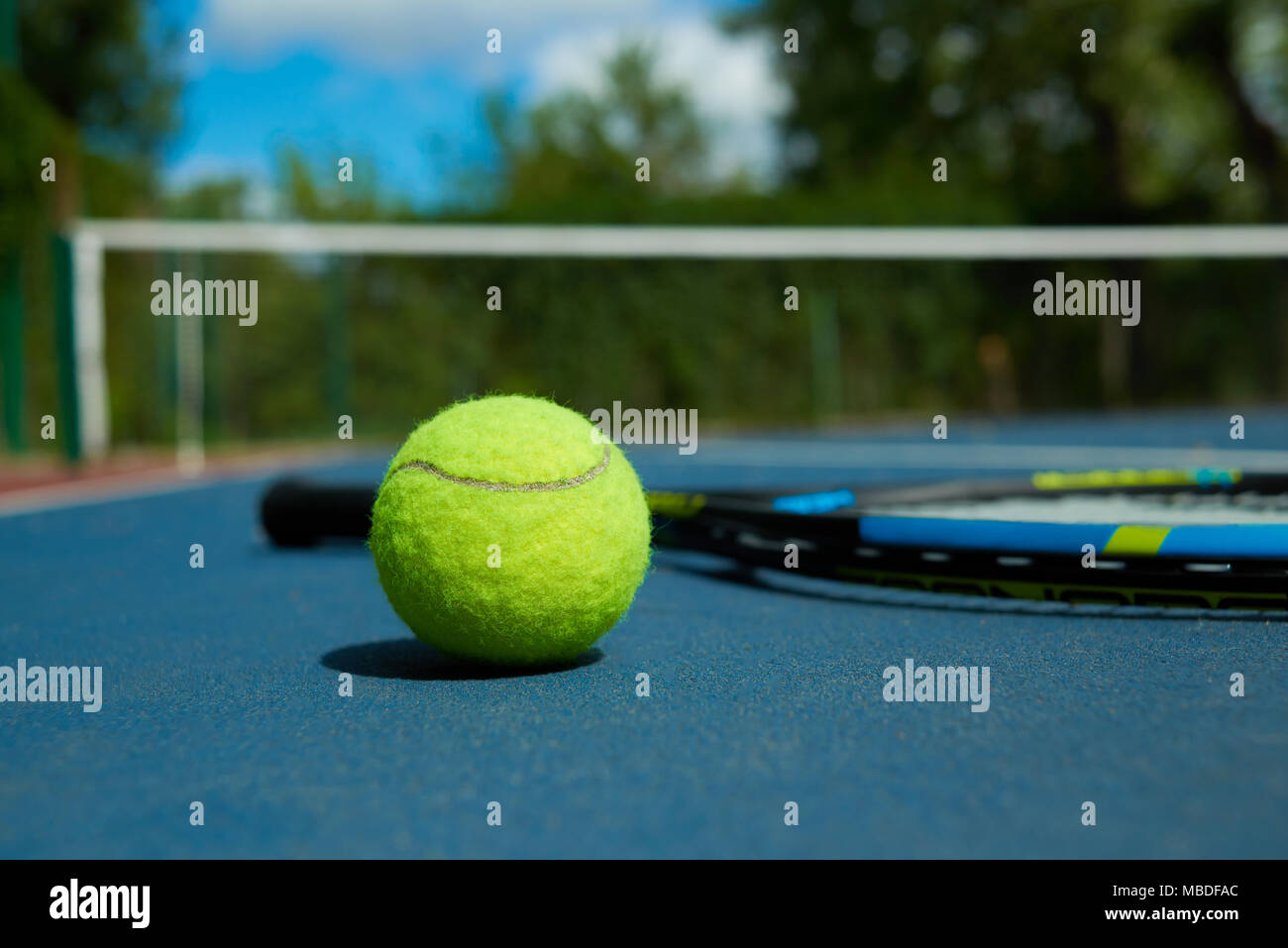 Close up of yellow ball is on tennis racket background, laying on blue tennis court carpet. Photo of professional sport equipment. Concept of tennis outfit photografing. - Stock Image