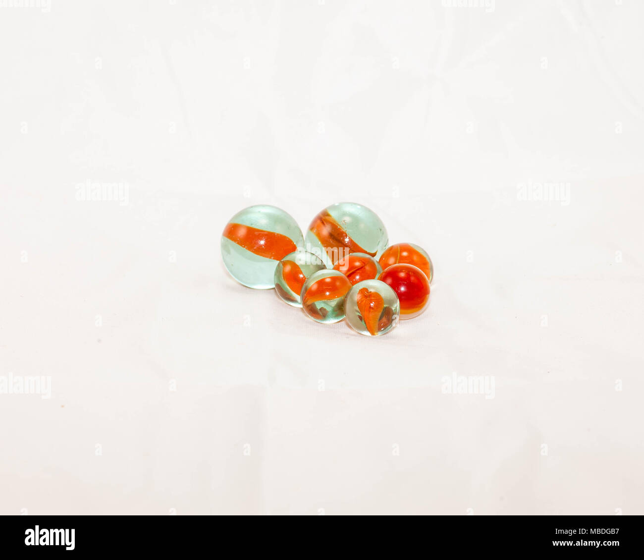 two sizes of orange cats-eye marbles at rest - Stock Image
