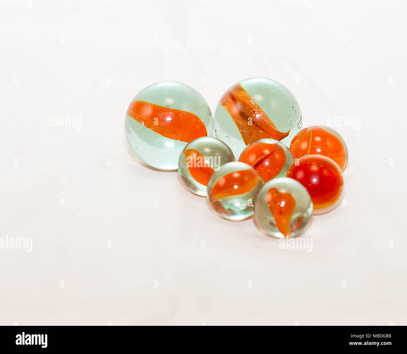 close up of two sizes of orange cats-eye marbles - Stock Image