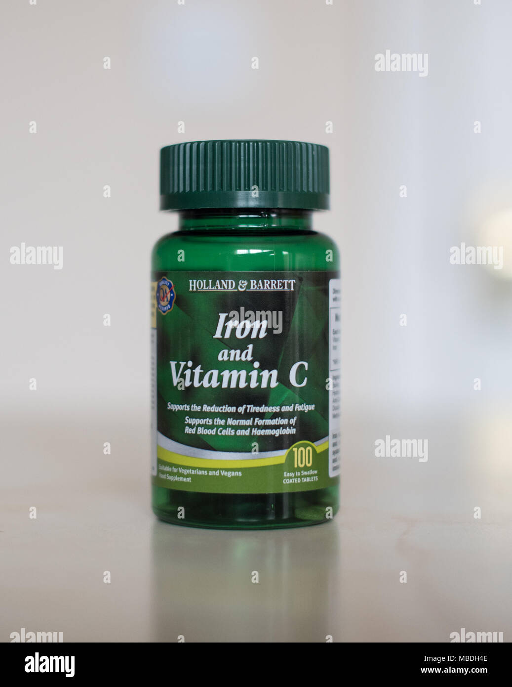 Vitamin C & Iron supplements in a clear bottle full of little tablets to make you feel better - Stock Image