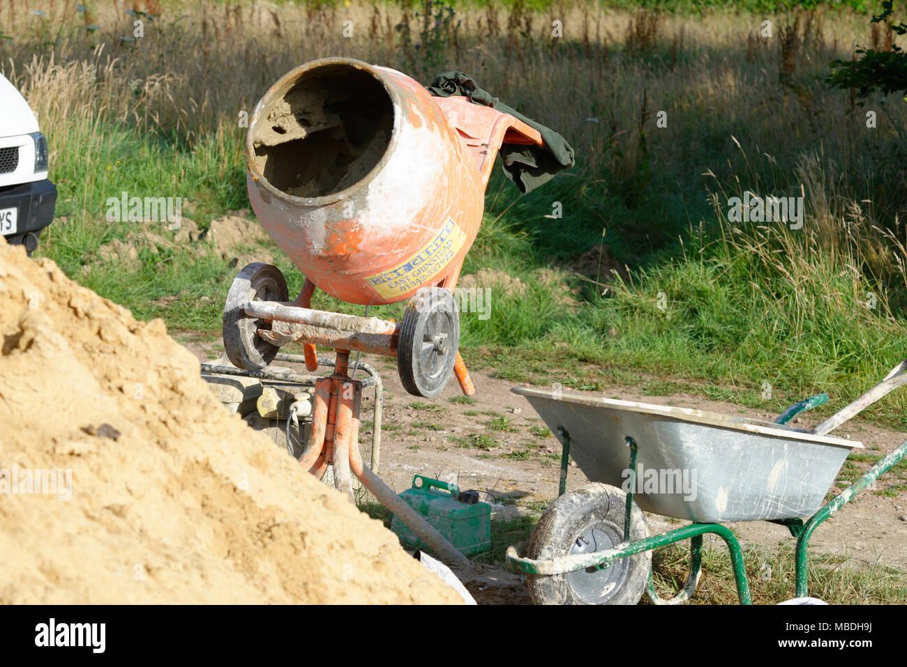 Orange cement mixer on site. - Stock Image