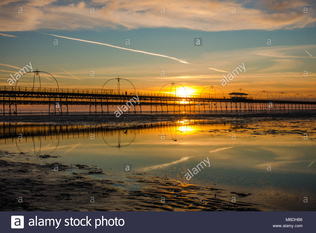 Southport Pier at sunset, showing the meal arches and stays of the bridge at sunset with a jet stream in the sky, which is reflected, England UK Stock Photo
