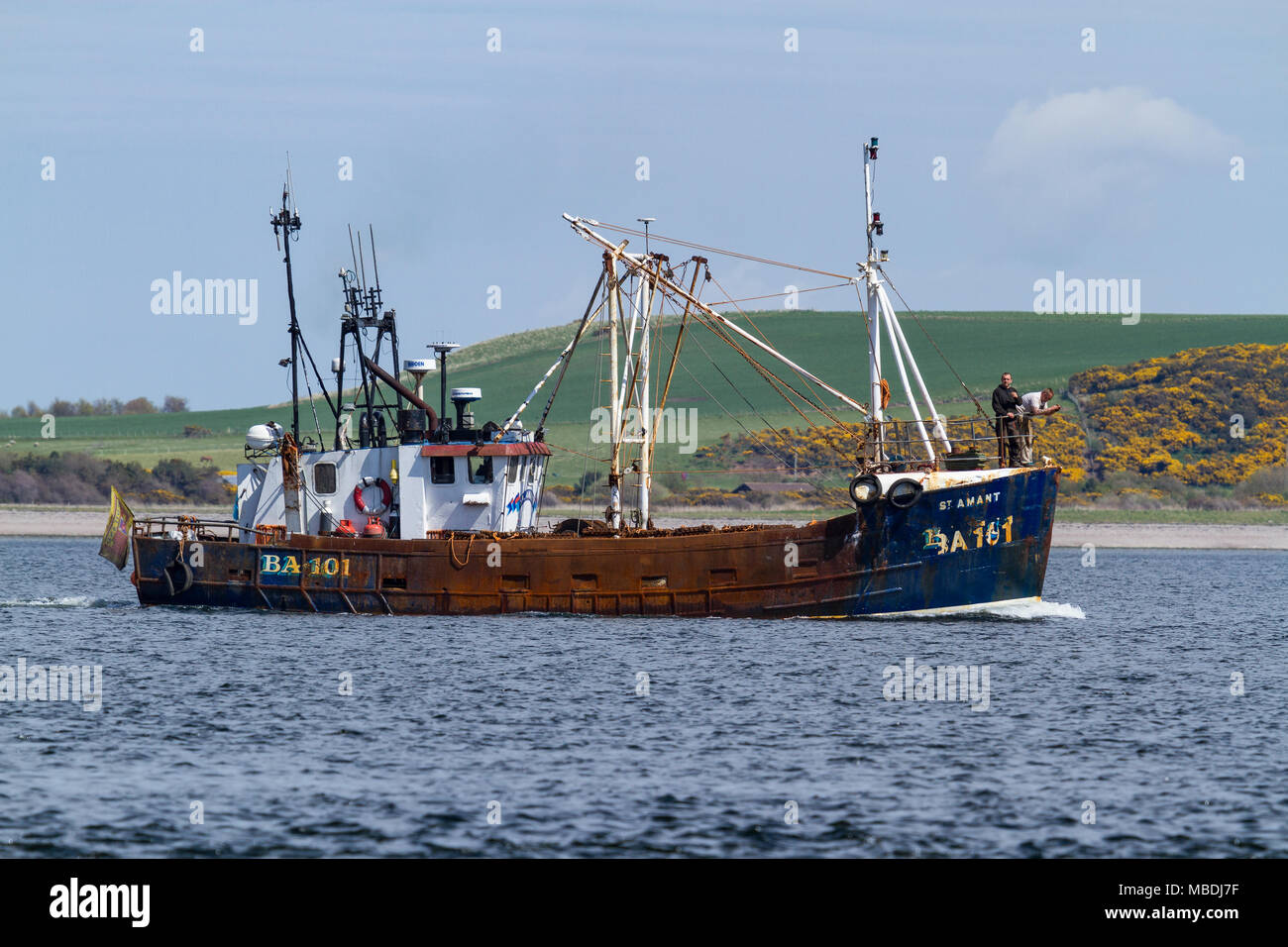 Fishing boat in the Moray Firth heading towards Inverness. Taken from Chanonry Point on the Black Isle, Scotland. - Stock Image