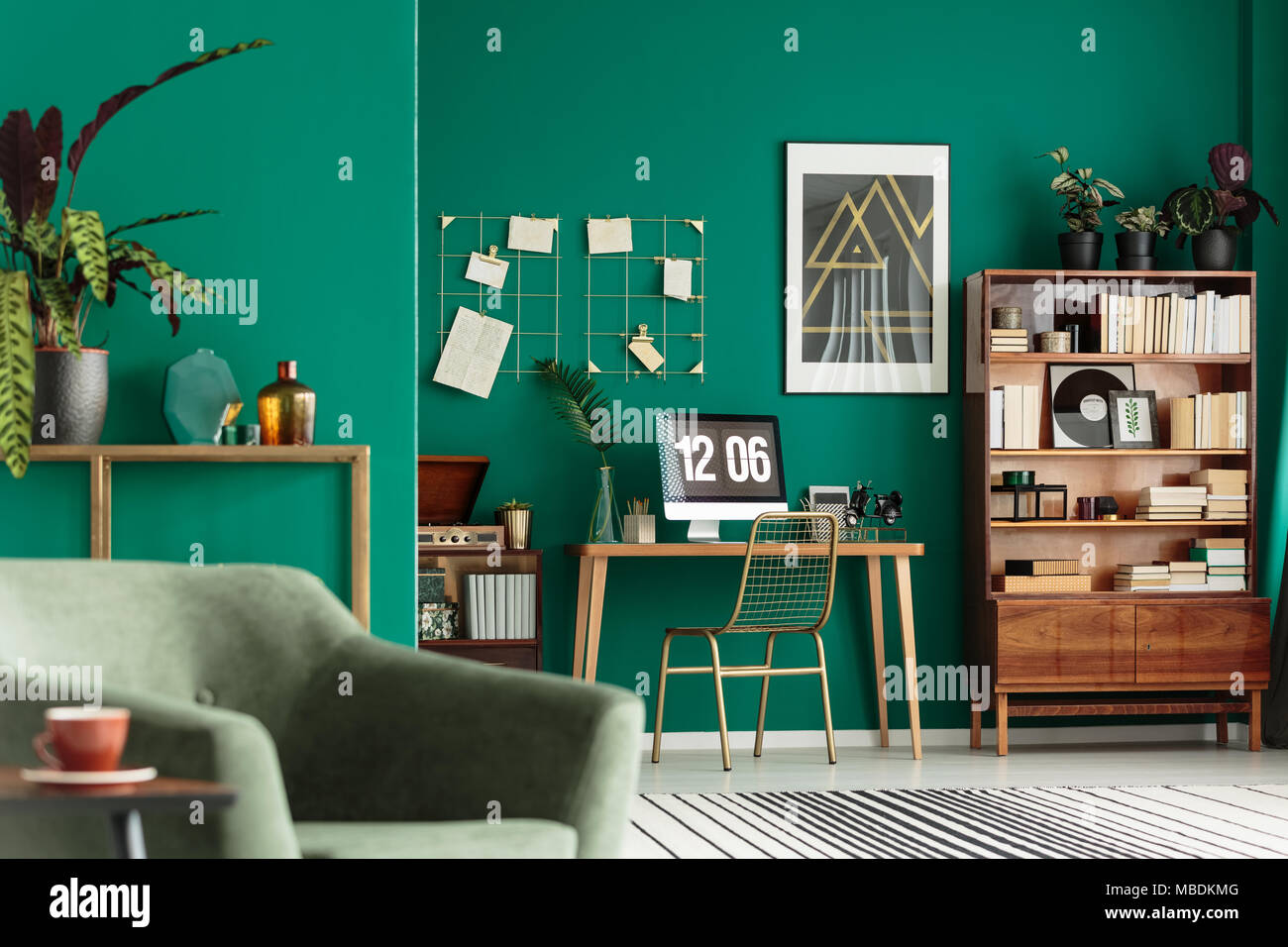 Green living room interior with books on wooden cupboard and desk for remote work - Stock Image