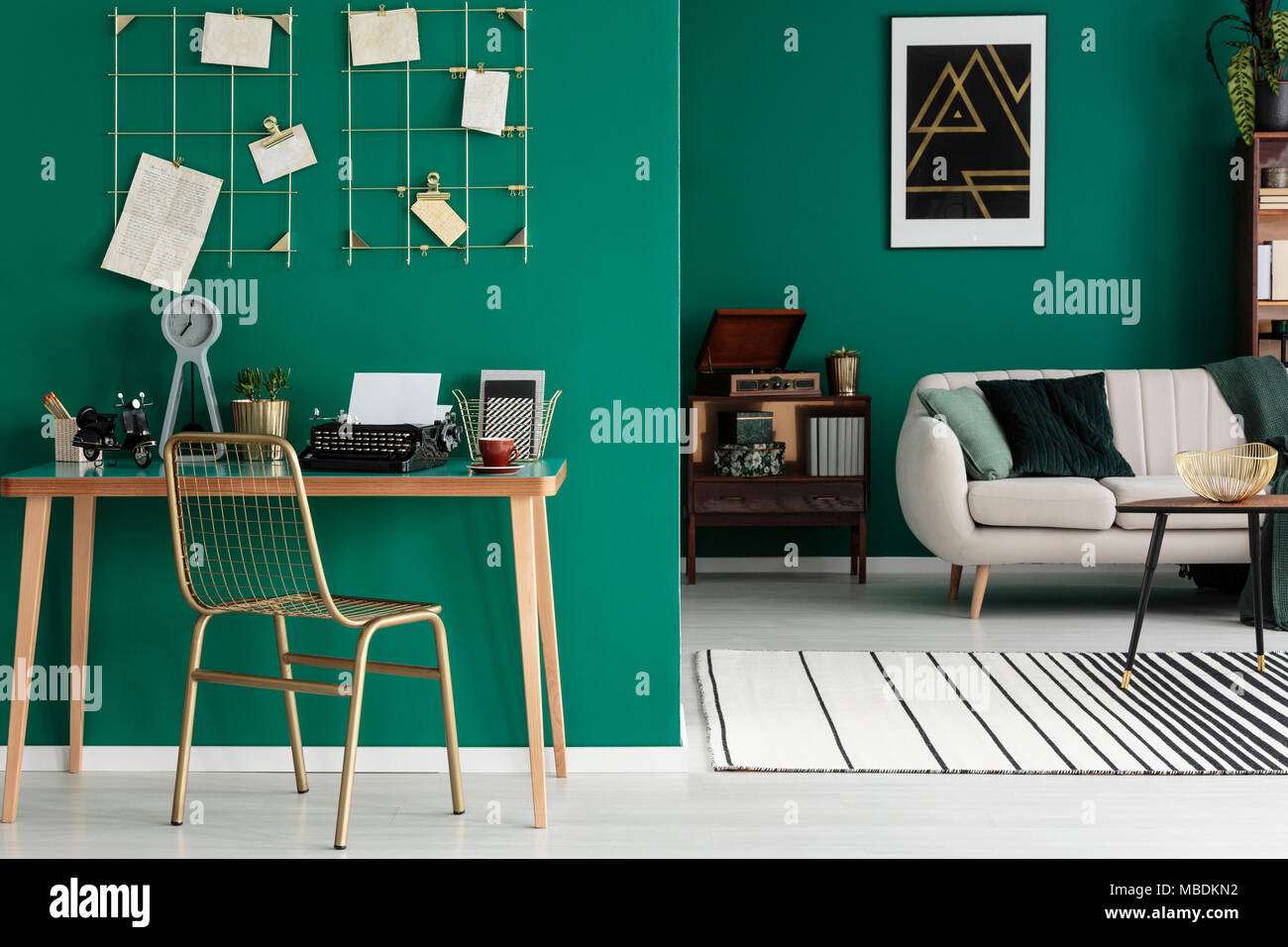 Gold, metal chair by a wooden desk with clock and typewriter in open space interior with carpet and bright sofa - Stock Image