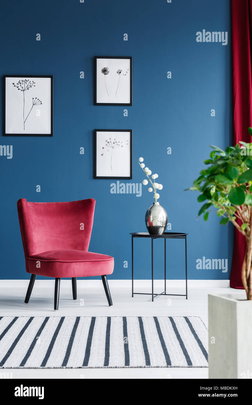 Red chair against blue wall with posters in elegant living ...