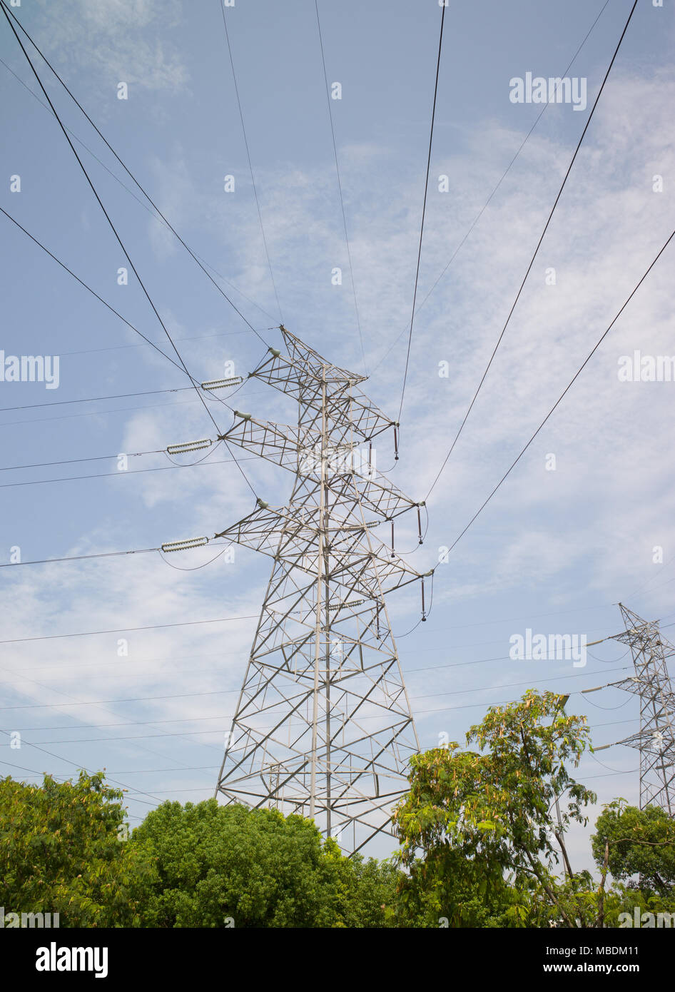 Electricity pylons and cables with blue sky and clouds in background - Stock Image