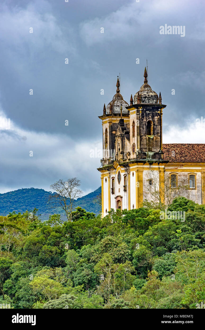 Ancient historical church high in one of the several mountains of the city of Ouro Preto with the vegetation and dark clouds in background - Stock Image