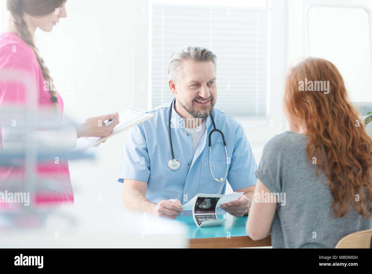 Optimistic doctor explaining ultrasound image to his patient and nurse taking notes - Stock Image