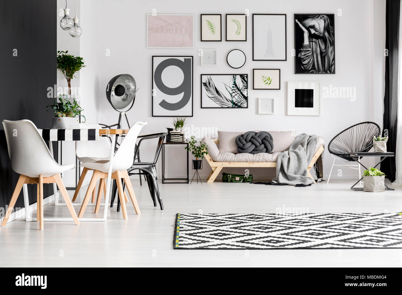 Art Gallery Dining Table With Chairs And Sofa With Blanket And Knot Pillow In A White Living Room Interior Stock Photo Alamy