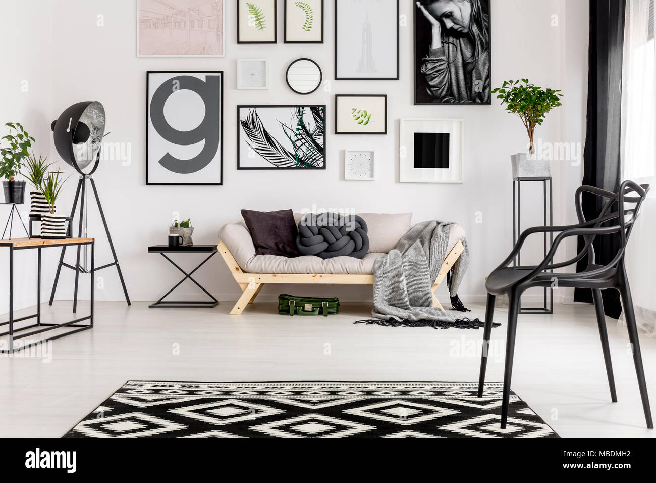 Comfy sofa with pillows, blanket, geometrical rug and posters in an artistic living room interior - Stock Image
