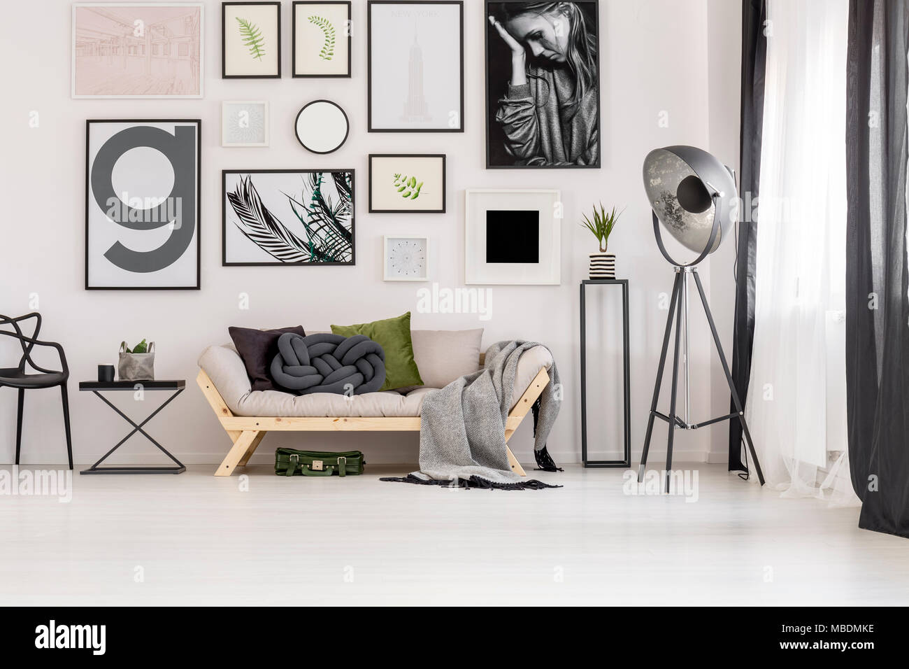 Green suitcase under a comfy sofa with pillows and blanket in a living room interior decorated with posters - Stock Image