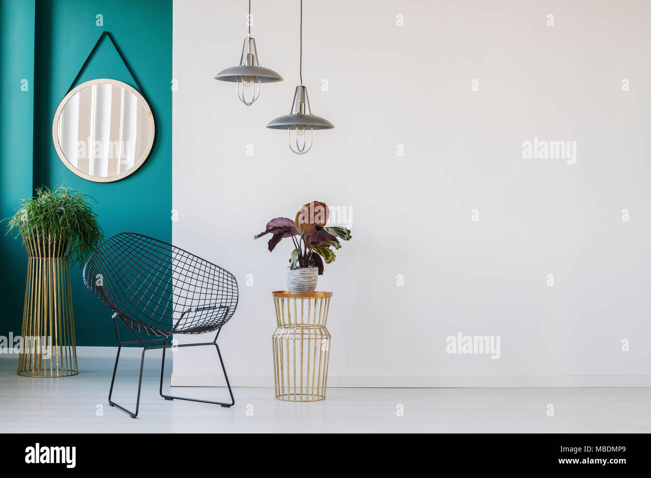 Plant on gold table next to black armchair in minimalist living room ...